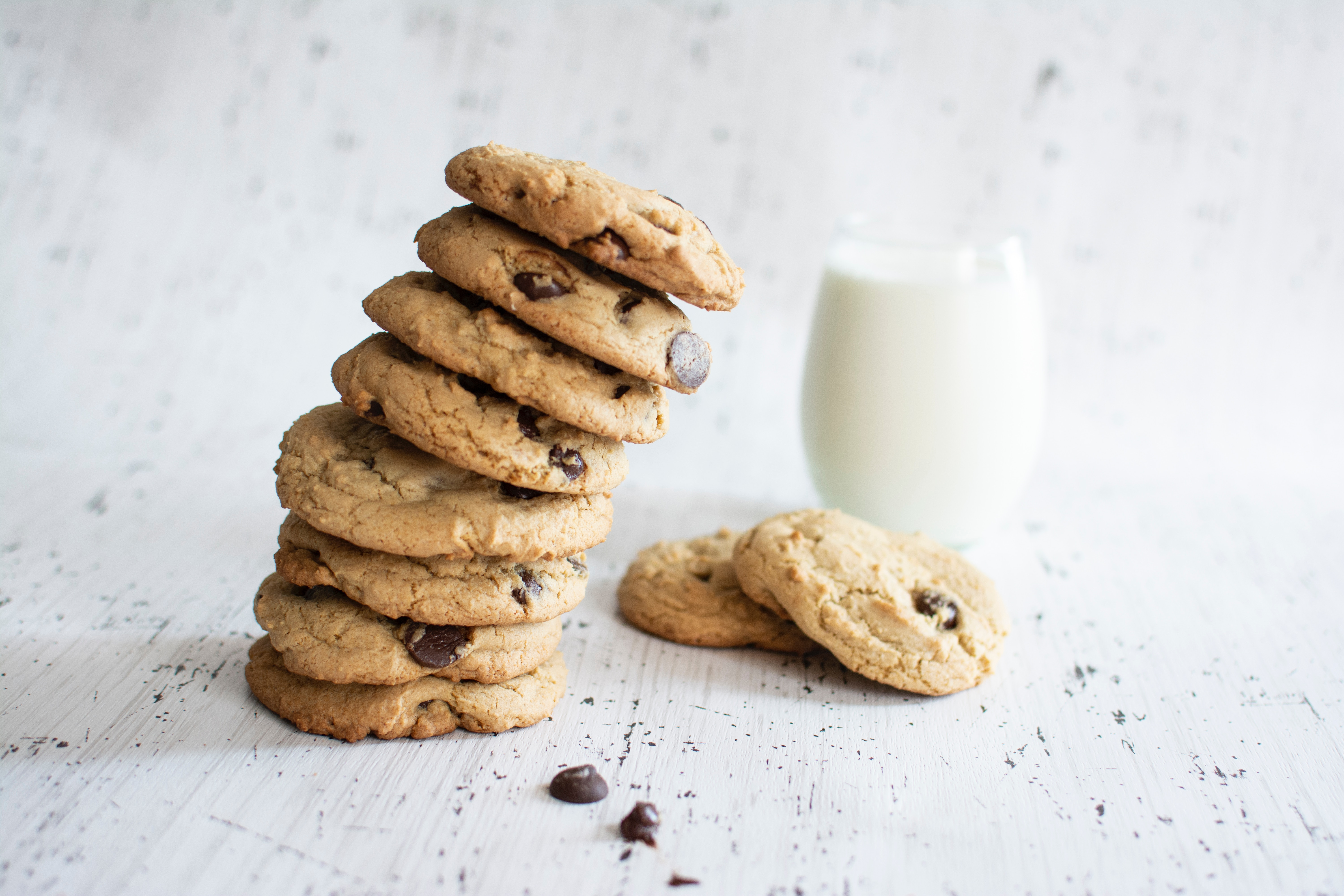 A leaning stack of chocolate chip cookies beside a glass of milk
