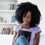 Young woman reading a book on an electronic device