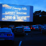 cars are in front of a drive-in movie theater screen displaying a welcome message