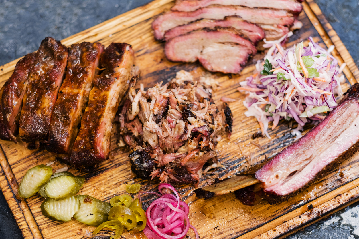 An assortment of barbecued meats and toppings on a cutting board