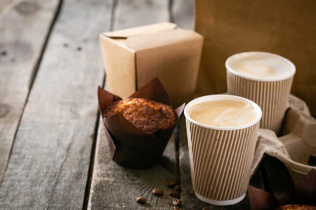 two takeout cups of coffee sit next to a muffin and takeout boxes