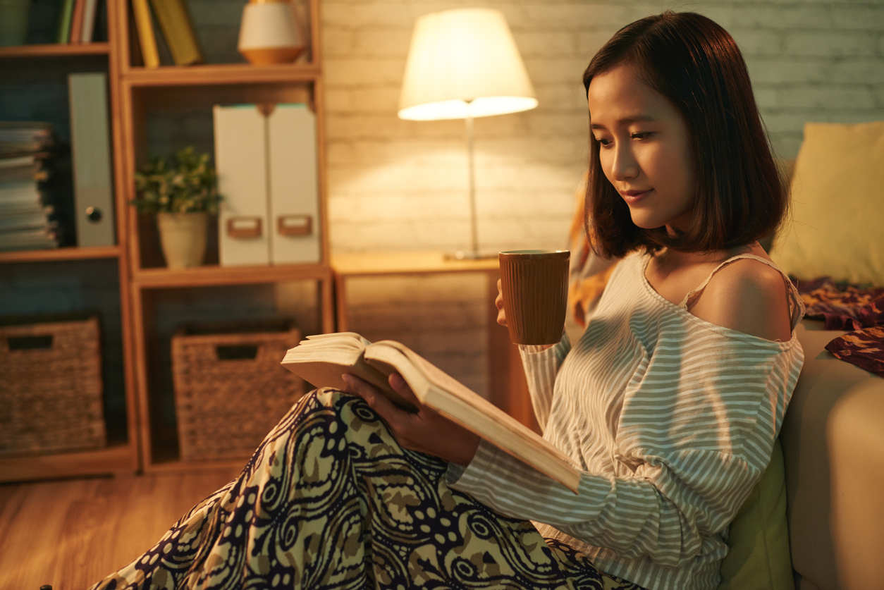 a woman drinks a mug of tea and reads a book at home