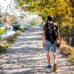 a person walks on a trail near water, wearing a backpack