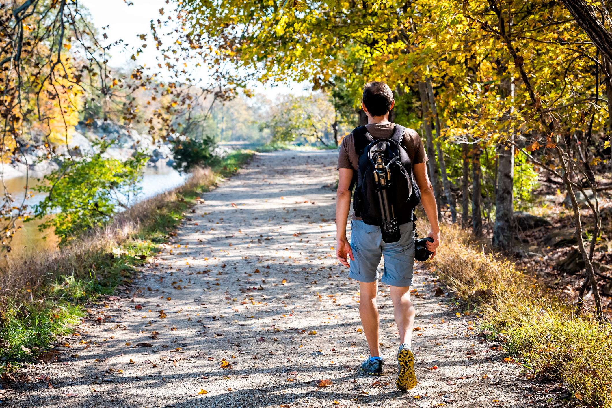 person walking with a backpack on a nature trail