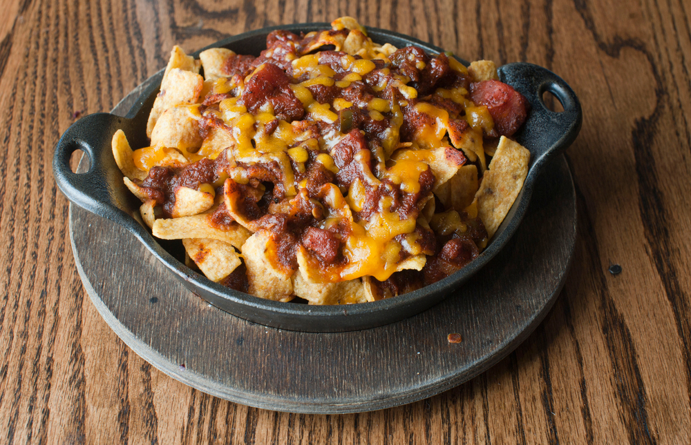 An overhead view of a serving of Frito pie with melted cheese