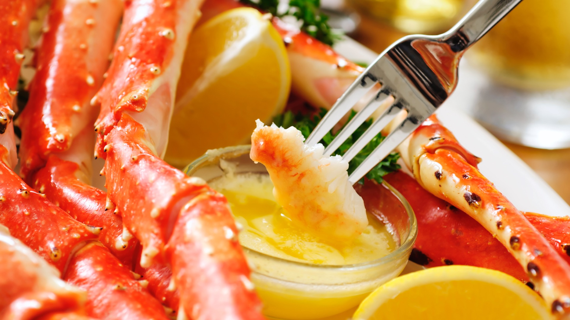 a fork dipping lobster in butter | lobster rolls in Austin