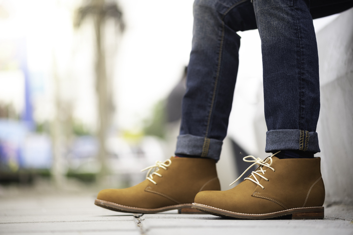 brown lace up boots on a person wearing jeans outside | Austin shoe stores