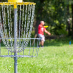 people are blurry in the background as they throw discs at the goal | disc golf in Austin