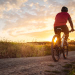 a person bikes on a trail at sunset | bike shops in Austin