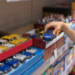 child chooses a toy car from a shelf | local Austin toy stores